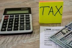 Feuille d'impôt 1040, dollars et une calculatrice sur un fond en bois image libre de droits