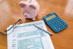 Feuille d'impôt d'IRS avec la tirelire et la calculatrice images libres de droits