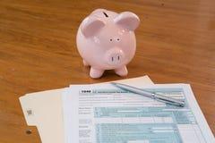 Feuille d'impôt d'IRS avec la tirelire et la calculatrice photo stock