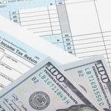 Feuille d'impôt 1040 avec deux 100 dollars de billets de banque Images libres de droits