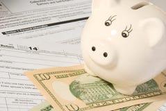 Feuille d'impôt de retour de personne avec l'argent et la barre porcine images stock