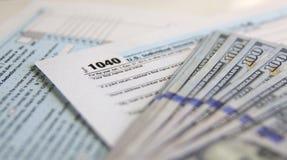 Feuille d'impôt des Etats-Unis 1040 avec 100 factures de dollar US Images stock