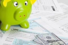 Feuille d'impôt des Etats-Unis d'Amérique 1040 avec la tirelire verte Photos stock