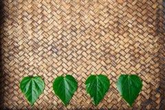 Feuille de forme de coeur sur le tapis en bambou Photographie stock libre de droits