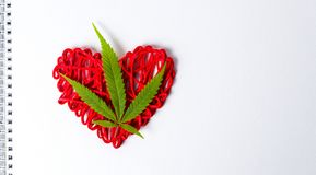 Feuille de marijuana sur une forme de coeur dans le carnet Photographie stock libre de droits