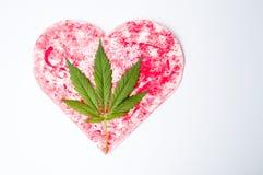 Feuille de marijuana sur une forme rouge de coeur Photographie stock libre de droits