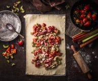 Feuille de pâte avec la rhubarbe et les fraises coupées en tranches Préparation de tarte de strudel sur la table de cuisine rusti images stock