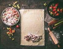 Feuille de pâte avec les ingrédients découpés de rhubarbe et de fraises pour le tarte de strudel, sur la table de cuisine rustiqu photographie stock libre de droits