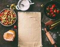 Feuille de pâte de pâtisserie sur la table de cuisine rustique avec des ingrédients de rhubarbe et de fraises pour le tarte de st photographie stock libre de droits