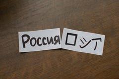 Feuille de papier avec une inscription : La Russie écrivant dans la traduction japonaise de kanji et de Russe - Russie image libre de droits
