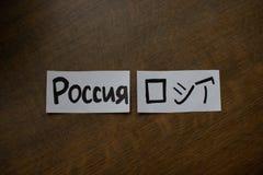 Feuille de papier avec une inscription : La Russie écrivant dans la traduction japonaise de kanji et de Russe - Russie photographie stock