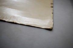 Feuille de papier beige sur un fond gris image stock