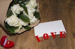 Feuille de papier blanche sur un fond en bois avec un bouquet de RO Photo libre de droits