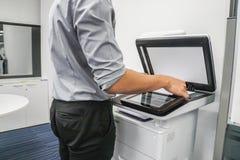 Feuille de papier de presse d'homme d'affaires sur l'imprimante pour les documents de copie et de balayage photo libre de droits