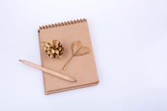 Feuille en forme de coeur, cône de pin et un crayon sur un carnet Photo libre de droits