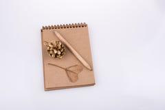 Feuille en forme de coeur, cône de pin et un crayon sur un carnet Photographie stock libre de droits
