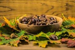 Feuille et châtaignes d'automne sur la table en bois Photographie stock