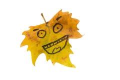 Feuille jaune avec une photo d'un visage heureux isolat Image stock
