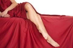 Feuille rouge de jambes de femme outre de côté de lit Photo stock