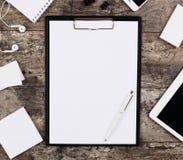Feuille vide de livre blanc dans un dossier d'agrafe entouré par des fournitures de bureau Photographie stock libre de droits