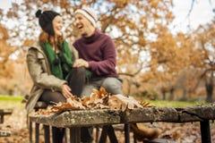 Feuilles au-dessus d'une table en bois en parc au premier tir Talki de couples Images stock