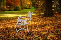 Feuilles blanches de banc et d'automne en parc photographie stock libre de droits