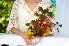 Feuilles d'érable d'automne chez des mains de la femme Photographie stock
