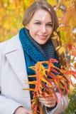 Feuilles d'automne élégantes de cueillette de jeune femme Photos stock