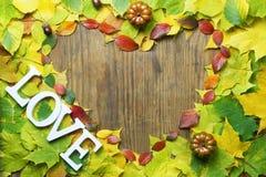 Feuilles d'automne dans la forme du coeur sur la table en bois Image stock