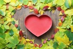Feuilles d'automne dans la forme du coeur sur la table en bois Photos libres de droits