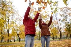 Feuilles d'automne de lancement de jeunes couples heureux en parc Photos stock