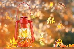 Feuilles d'automne soufflant autour d'une lanterne Photographie stock