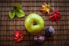 Feuilles d'automne vert pomme sur le fond en bois Photos stock