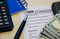 Feuilles d'impôt 1040, dollars, bloc-notes de calculatrice et stylo sur une table en bois photo stock