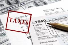 Feuilles d'impôt et argent  Photos stock