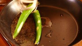 Feuilles de cari étant jetées dans une casserole avec des épices, des piments et des condiments banque de vidéos