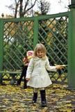 Feuilles de jaune de petite fille et d'automne Photo stock