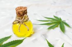 Feuilles de pétrole et de marijuana de cannabis sur le blanc Photos stock