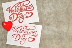 Feuilles de papier avec police peinte de Saint-Valentin d'inscription une belle, rouge Sur un peint en encre et doucement sur l'a photos stock