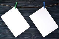 Feuilles de papier blanches sur un mur en bois Images stock