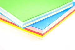 Feuilles de papier coloré sur un fond blanc d'isolement Images libres de droits