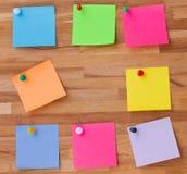 Feuilles de papier colorées sur le panneau en bois Image stock