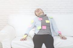 Feuilles de papier jaunes, vertes et roses sur la femme qui dort et épuisé du travail image libre de droits