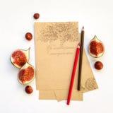 Feuilles de papier vides avec des crayons, des fruits de figue et des châtaignes sur le fond Configuration plate, vue supérieure Photo libre de droits