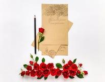 Feuilles de papier vides avec les roses rouges sur le fond blanc Configuration plate, vue supérieure Image stock