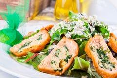 Feuilles de salade avec des rouleaux de saumons Photos stock