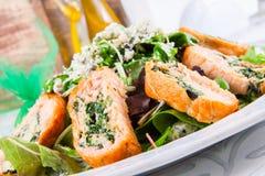 Feuilles de salade avec des rouleaux de saumons Photographie stock libre de droits