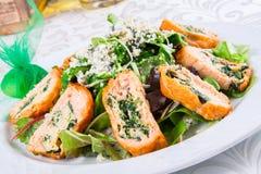 Feuilles de salade avec des rouleaux de saumons Photo stock