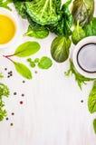 Feuilles de salade avec la table en bois blanche de dressingson Photographie stock libre de droits