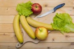 Feuilles de salade, pommes, banane, couteau et un plat étripant en bois sur le fond en bois Images libres de droits